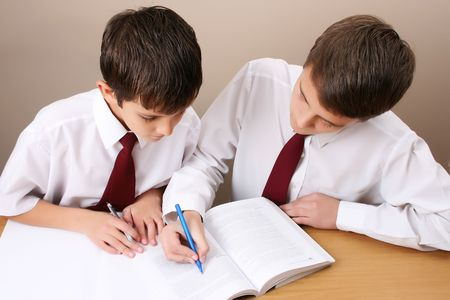 Teenage School boy busy with his homework, wearing uniform