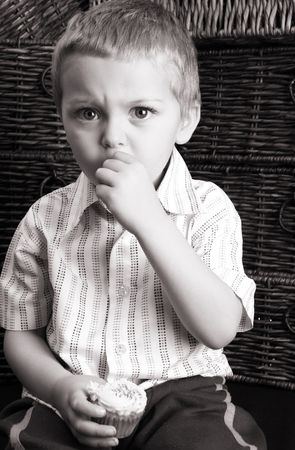 Serious toddler eating a cup cake, sitting against drawers photo