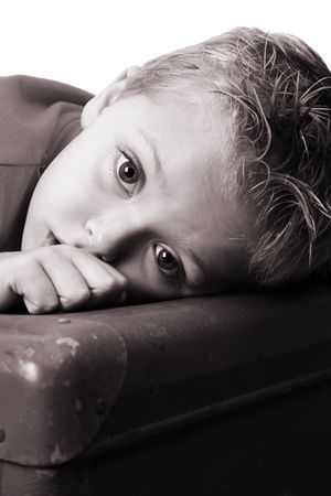 antique suitcase: Beautiful blond toddler lying on an antique suitcase