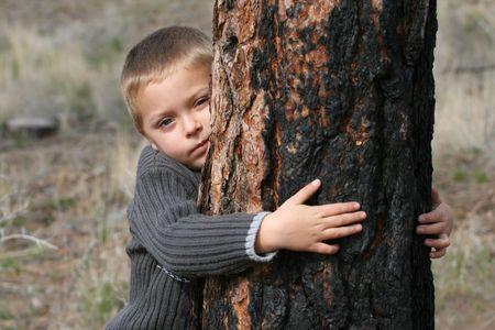 Little boy hugging a tree in the woods
