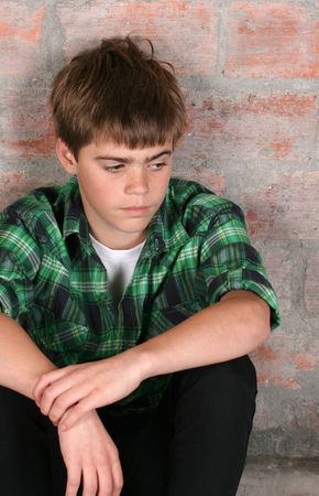 sad child: Serious teenager sitting alone against a brick wall Stock Photo