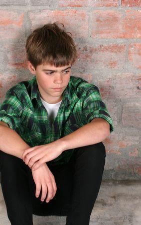 Ernsthafte Teenager, die allein gegen eine Ziegelmauer sitzen Standard-Bild - 6878622
