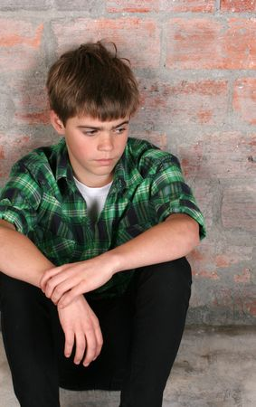 Serious teenager sitting alone against a brick wall Stockfoto