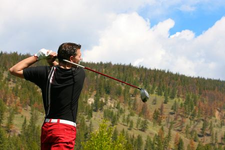 Young golfer in his follow through position with a driver Stock Photo - 6959050