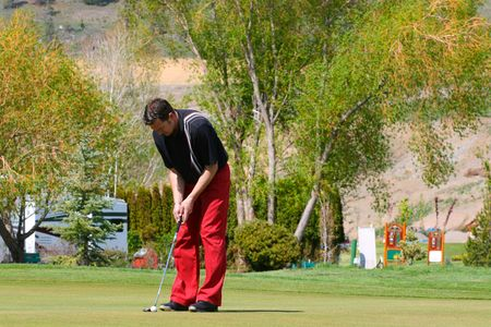 Young male golfer playing a round of golf photo