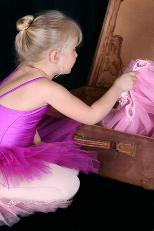 antique suitcase: Little blond ballerina looking for a costume in an antique suitcase