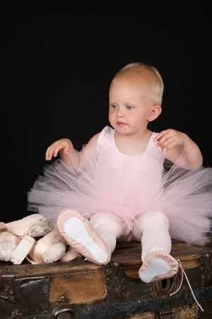 pointes: Beautiful blond baby wearing a ballet costume sitting ontop of antique trunk