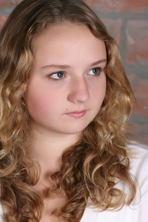 Beautiful teen with curly hair against a brick wall background  photo