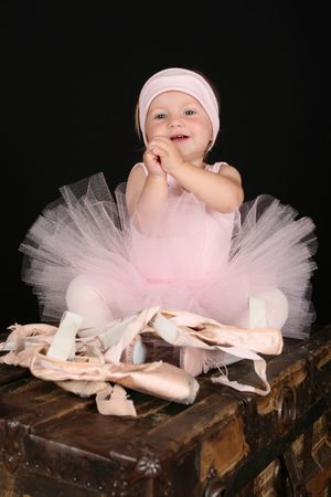 Baby ballerina sitting on an antique trunk