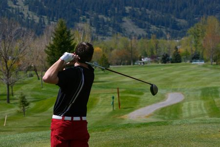 Young golfer in his follow through position with a driver  Archivio Fotografico