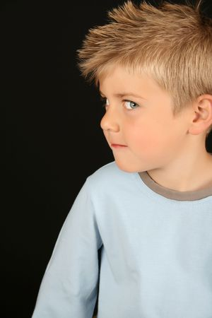 maliziosa: Carino ragazzo biondo su sfondo nero  Archivio Fotografico