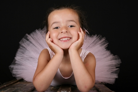 Cute brunette ballet girl wearing a pink ballet costume Stock Photo