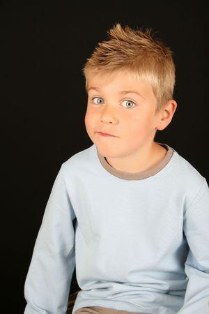 mischievous: Cute blond boy on a black background