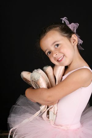 Cute brunette ballet girl holding lots of pointe shoes