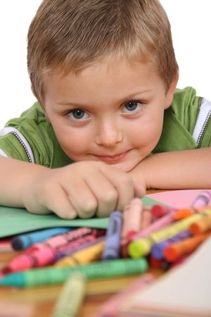 coloring sheets: Young blond boy resting his head on his hand, crayons and colorful paper in front of him