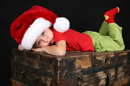 Sad boy wearing a christmas hat, ontop of an antique trunk photo