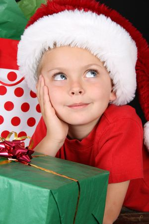 Cute caucasian boy wearing a christmas hat looking up photo