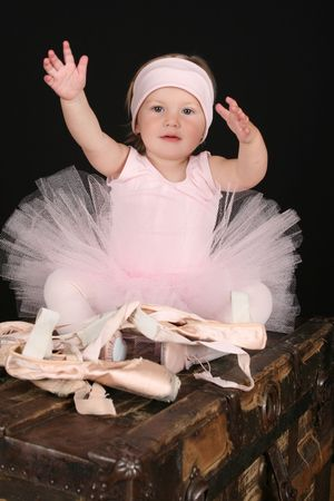 Baby ballerina sitting on an antique trunk  photo