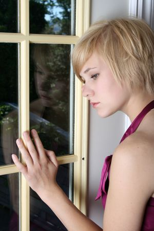 Beautiful blond female leaning against a door, expressing sadness and loneliness Stock Photo - 7802078