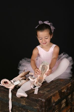 pointe shoes: Cute little brunette girl trying on ballet pointe shoes Stock Photo