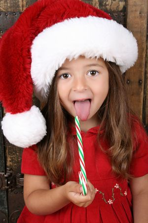 tongue out: Cute brunette girl eating Christmas candy and sticking her tongue out