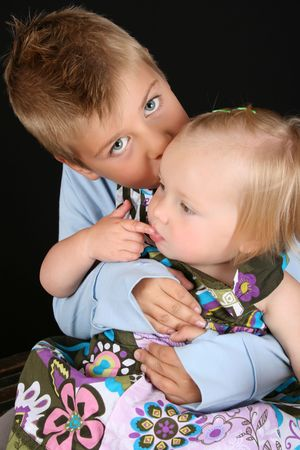 Cute brother holding his toddler sister in his arms  photo