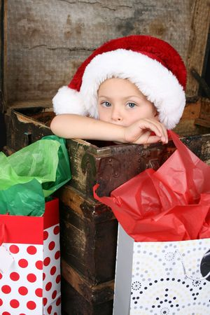 Serious boy sitting inside an antique trunk wearing a christmas hat Stock Photo - 7853541