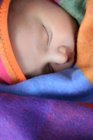 Beautiful newborn boy wrapped in a colorful blanket photo