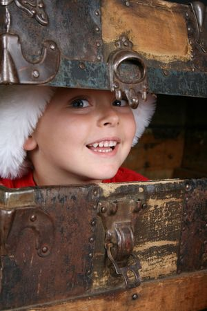 Beautiful blue eyed boy peeping from within an antique trunk  photo