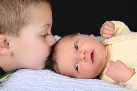 sibling: Blond boy with his newborn baby brother