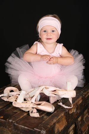 Baby ballerina sitting on an antique trunk