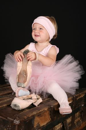 Blond toddler wearing a tutu holding pointe shoes photo