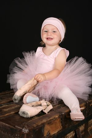Blond toddler wearing a tutu holding pointe shoes Stock Photo