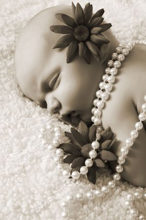 Beautiful newborn baby girl with flowers and pearls photo