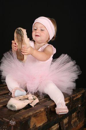 Blond toddler wearing a tutu holding pointe shoes Reklamní fotografie