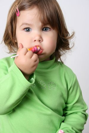 Toddler girl with chubby cheeks eating a sticky lollipop  Stock Photo - 7941667