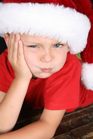 Bored little boy wearing a fluffy Christmas hat Stock Photo - 8037704