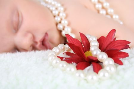 Beautiful baby girl sleeping, pearls draped with flower.  FOCUS ON FLOWER AND PEARLS. photo