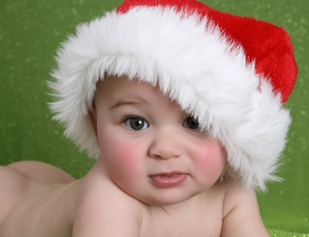 Cute baby boy wearing a christmas hat on green background photo