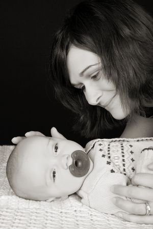 Beautiful mother and son against a black background photo