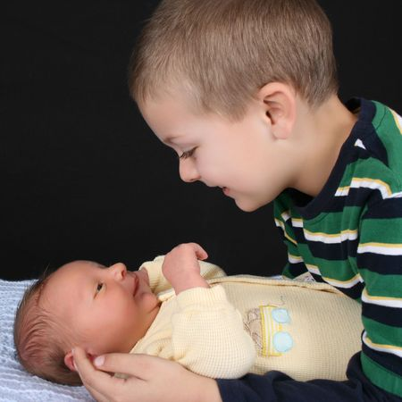 Blond boy with his newborn baby brother  Banco de Imagens
