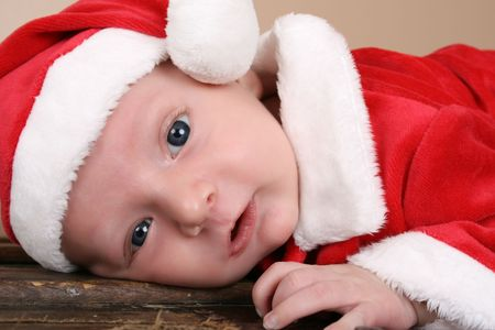 Beautiful six week old baby boy wearing a Christmas suit photo