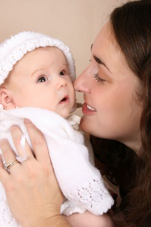 Beautiful brunette mother holding her two month old baby girl Stock Photo - 8240571