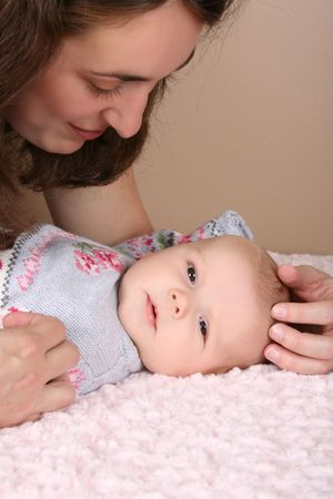 Beautiful brunette mother looking at her two month old baby girl  photo