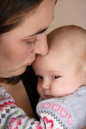 Beautiful brunette mother holding her two month old baby girl  photo