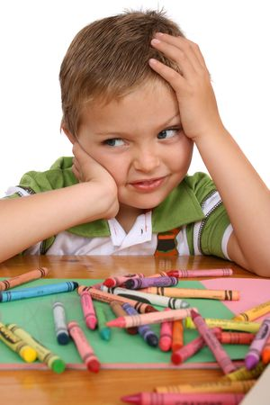 fedup: Young blond boy resting his head on his hand, crayons and colorful paper in front of him