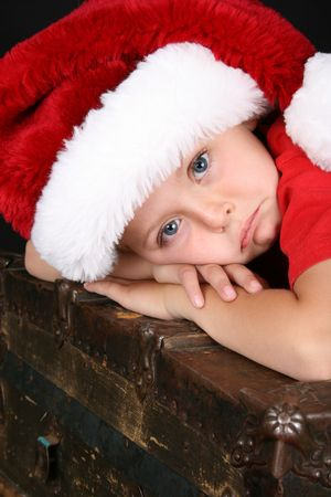 Beautiful boy lying on an antique chest with a sad expression