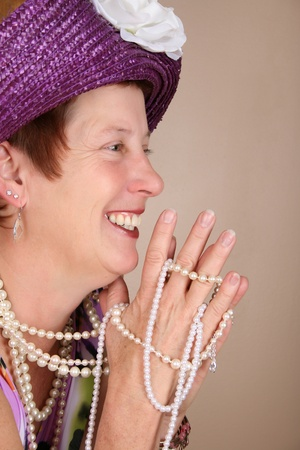 Adult female wearing a purple hat and pearls photo