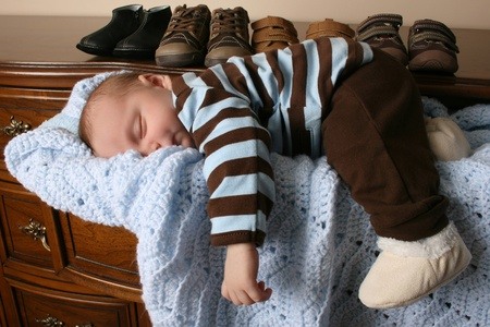 Month old baby boy sleeping in a drawer photo