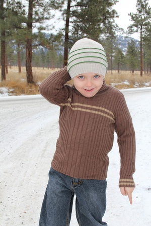 Warmly dressed boy playing outside in the snow Stock Photo - 8900384